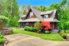 House with beautiful curb appeal. Clapbord siding brown house with green lawn and amazing blooming trees. View from the driveway Royalty Free Stock Image