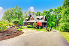 House with beautiful curb appeal. Clapbord siding brown house with green lawn and amazing blooming trees. View from the driveway Royalty Free Stock Photos