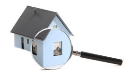 House behind a magnifying glass. On white royalty free stock photos