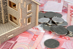 House with bill and coins. House model and lot of money, chinese currency, including bills and coins, means payment, real estate market and expensive concept Stock Photos