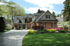 House with Black Shutters. Red brick house with black shutters and pretty manicured lawn / garden stock photo