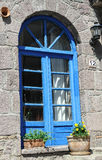 House with Blue Door. Famous Assos rock house with blue window and door frame and decorated with flowers in Assos,Turkey royalty free stock photos