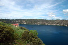 house on a blue lake royalty free stock photos