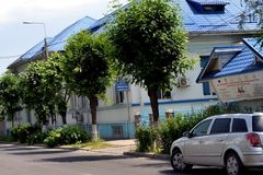 House with blue roof in town. Renovated old house with basement, ground floor and attic. Blue roof material green foliage contrasts the trees on the street stock photos
