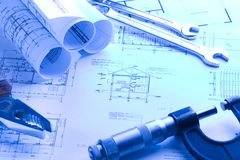 House blueprint with micrometer. House blueprint rolls with micrometer and Wrench in blue light stock photography