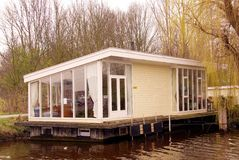 House boat. A house boat at the waterside and a wwwping willow Stock Images