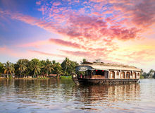 House boat in backwaters. Near palms at dramatic sunset sky in alappuzha, Kerala, India Royalty Free Stock Images