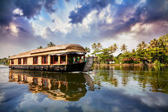 House boat in backwaters. Near palms at cloudy blue sky in Alappuzha, Kerala, India Royalty Free Stock Images