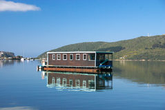 House Boat on Knysna Lagoon. A house boat sits in the placid water of Knysna Lagoon in South Africa Royalty Free Stock Image