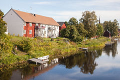 House and boat at the river. View over village in sweden, reflection in the water Royalty Free Stock Image