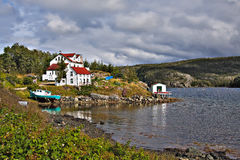 House and boat by water. Bed and breakfast home in Coffee Cove, West Newfoundland, Canada Stock Photo