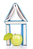 House from books. House from three blue books and green apple on white Stock Photos