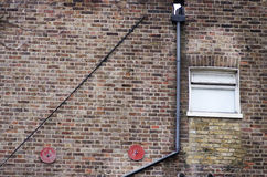 House brick wall with white small window and pipes, England London. Royalty Free Stock Photo