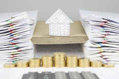 House on brown envelope between paperwork have blur calculator foreground. House on brown envelope between overload of old paperwork have blur step of gold coins stock images