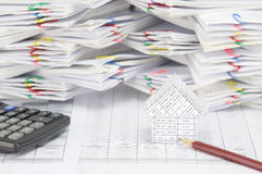 House with brown pencil and calculator on finance account. Have blur overload of paperwork with colorful paperclip as background stock photography