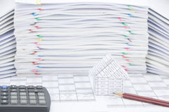 House and brown pencil with calculator on finance account. Have blur pile of paperwork as background royalty free stock photo