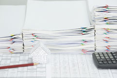 House with brown pencil and calculator on finance account. Have overload of paperwork with colorful paperclip as background stock photo