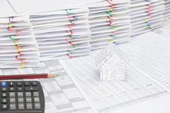 House with brown pencil and calculator on finance account. Have pile of document with colorful paperclip as background royalty free stock photography