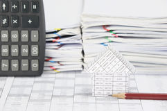 House with brown pencil. On finance account have blur calculator place vertical and overload of paperwork with colorful paperclip as background Stock Photo