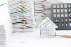 House and brown pencil have blur calculator as background. House and brown pencil on finance account have blur calculator and pile of paperwork as foreground and stock images