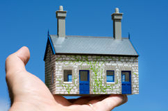House bubble. Man's hand hold a toy house against blue sky. Concept photo of Real estate market bubble , booming, money,price, rent, grid, home, house, housing Royalty Free Stock Images