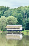 House build on water, straw roof, near lake and green forest Royalty Free Stock Photography