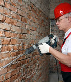 House-builder in uniform and red helmet working with a plugger Royalty Free Stock Photography