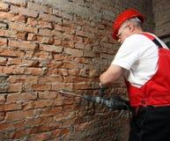 House-builder in uniforme che funziona con un plugger Fotografia Stock