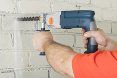 House-builder working with a perforator. Builder hold perforator and drilling brick wall Stock Photography