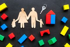 House building concept. Family cutout among colorful toy bricks on black background top view stock images