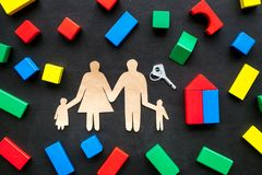 House building concept. Family cutout among colorful toy bricks on black background top view stock photo