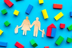 House building concept. Family cutout among colorful toy bricks on blue background top view stock photo