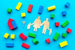 House building concept. Family cutout among colorful toy bricks on blue background top view stock image