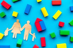 House building concept. Family cutout among colorful toy bricks on blue background top view royalty free stock photos