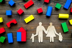 House building concept. Family cutout among colorful toy bricks on dark wooden background top view royalty free stock photos