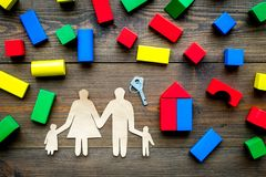 House building concept. Family cutout among colorful toy bricks on dark wooden background top view stock photos
