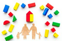 House building concept. Family cutout among colorful toy bricks on white background top view royalty free stock images