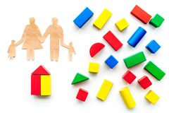House building concept. Family cutout among colorful toy bricks on white background top view stock images