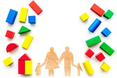 House building concept. Family cutout among colorful toy bricks on white background top view copy space royalty free stock photography