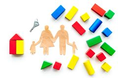 House building concept. Family cutout among colorful toy bricks on white background top view copy space stock photos