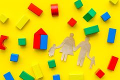 House building concept. Family cutout among colorful toy bricks on yellow background top view royalty free stock photo