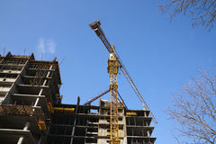 House and building crane. Skyscraper building by the building crane Royalty Free Stock Photography