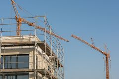 House building with two tower cranes stock photo