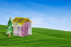 House built with banknotes lying between green hil Royalty Free Stock Photos