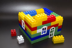 House built from children's construction kit. On a black background Stock Photos