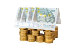 House built of coins and banknotes isolated Stock Image