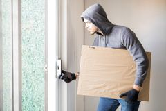 House burglar getting away. Man wearing a hoodie stealing some stuff from a house and leaving with a piece of art Stock Images