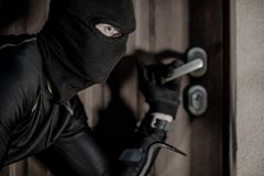 House Burglar in Mask. Taking Action. Checking House Doors. House Burglary Concept Stock Photo