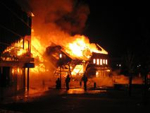 House in a burning inferno. Building in full flaming inferno, and the firefighters fighting to get control of the flames Stock Images
