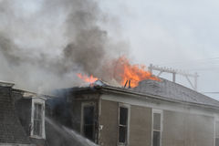 Roof top of house burning. Top of a house on fire burning, engulfed in flames Royalty Free Stock Photo